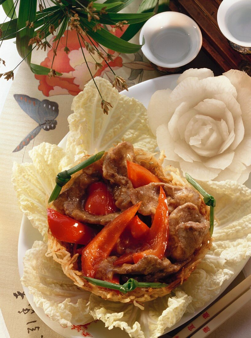 Meat with peppers in potato nest and radish roses