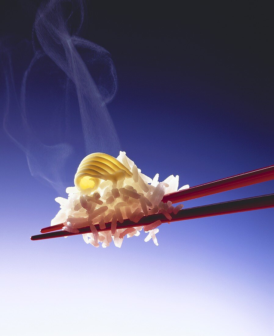 Steaming rice with butter curl on red chopsticks