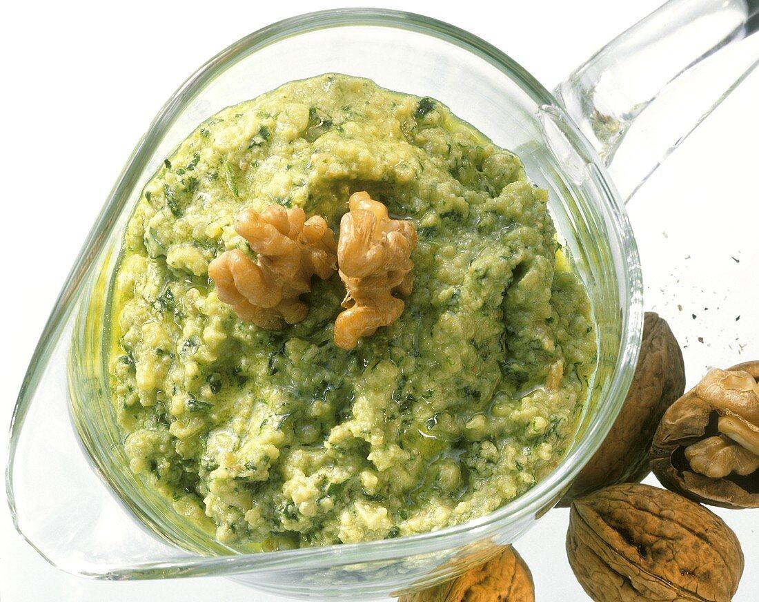 Walnut sauce (salsa di noci) in glass jug with walnut kernels