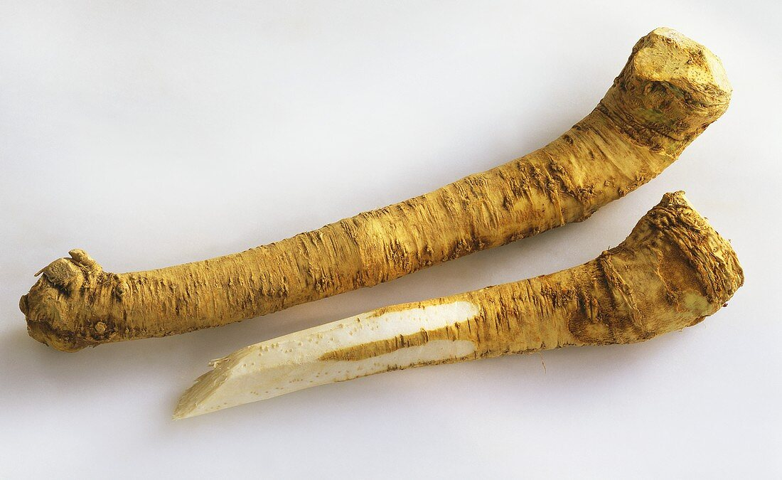 Two horseradish roots, one half peeled