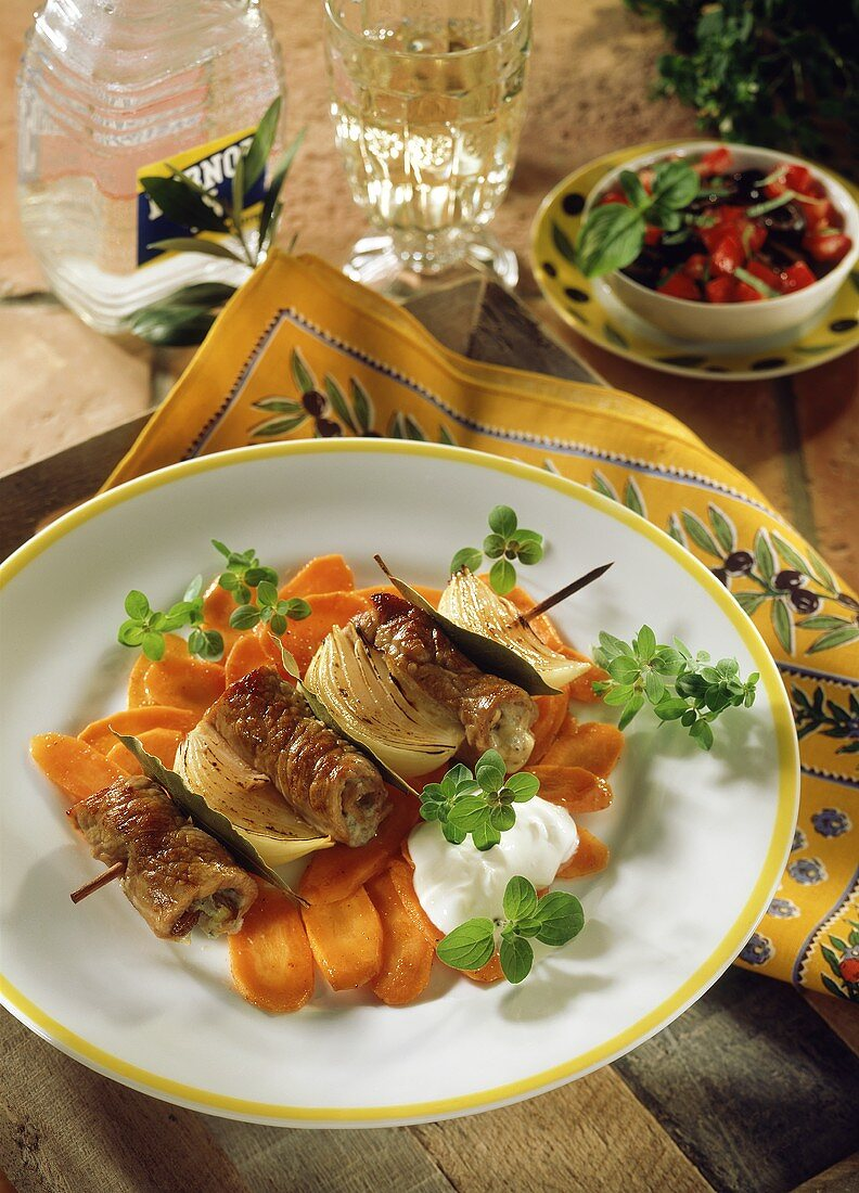 Veal roll kebab with onions & bay leaf on carrot crisps