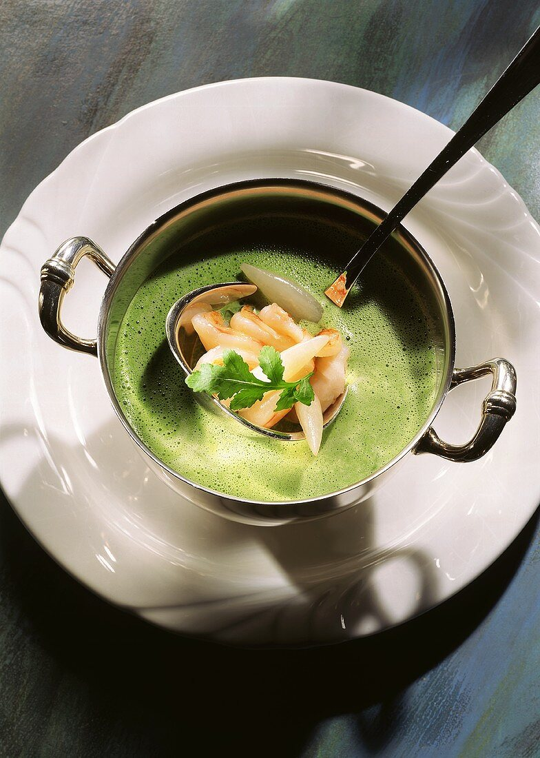 Cream of rocket soup with white radishes & shrimps on ladle