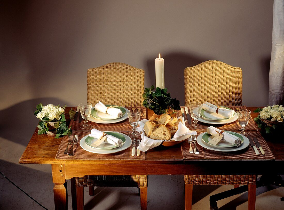Laid table with plates, napkins and burning candle