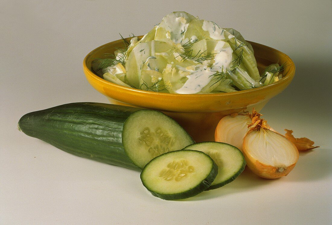 Cucumber salad with onions, dill & cream dressing in bowl
