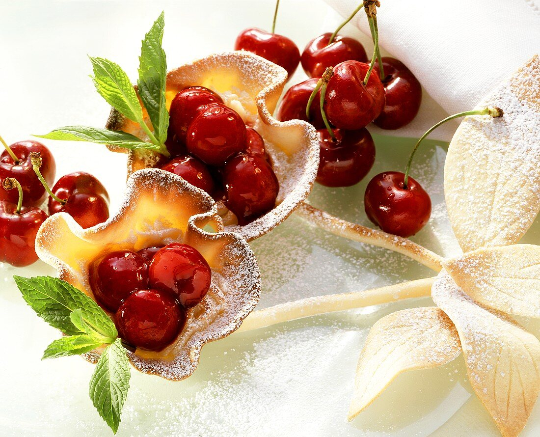 Cherry tartlet with stalk, icing sugar and herb leaves