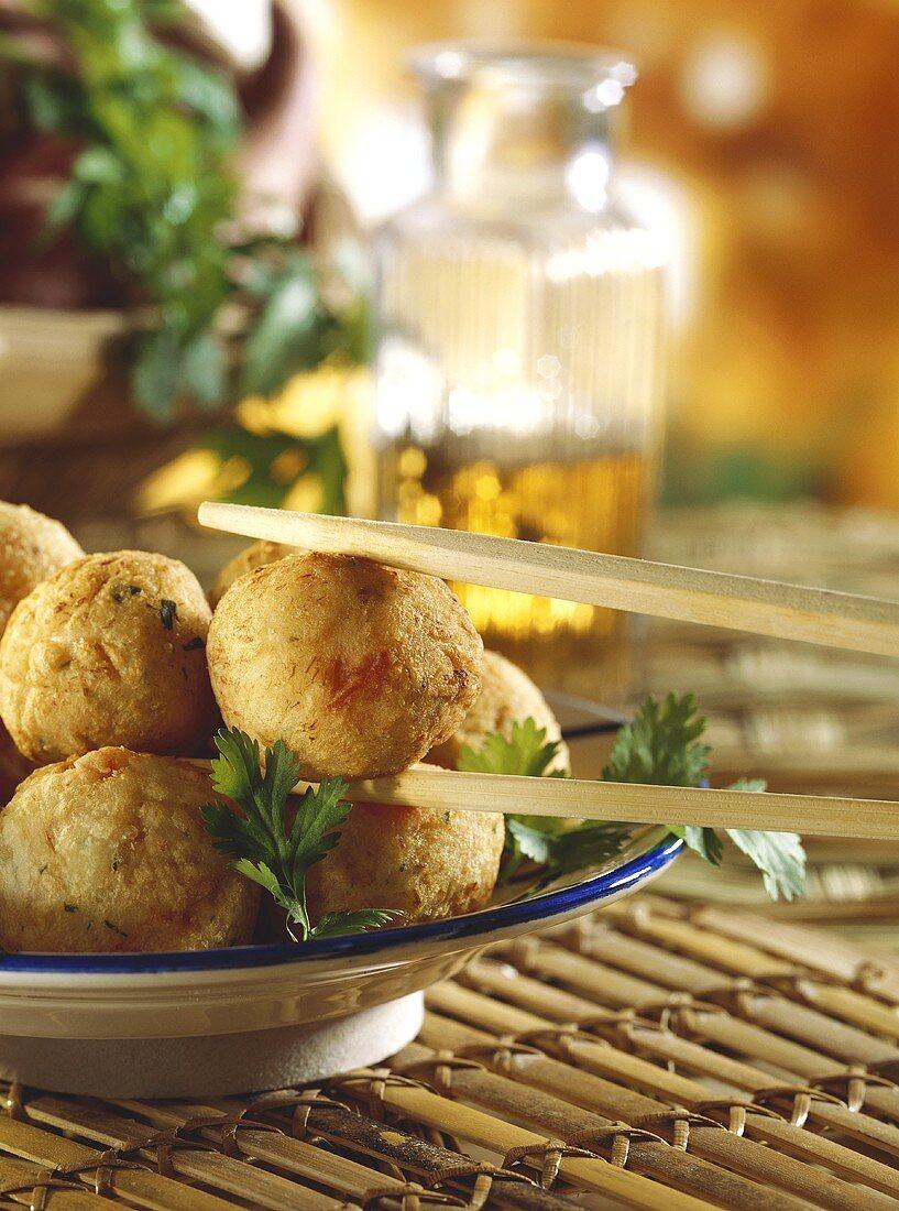 Deep-fried sweet potato balls, one between chopsticks