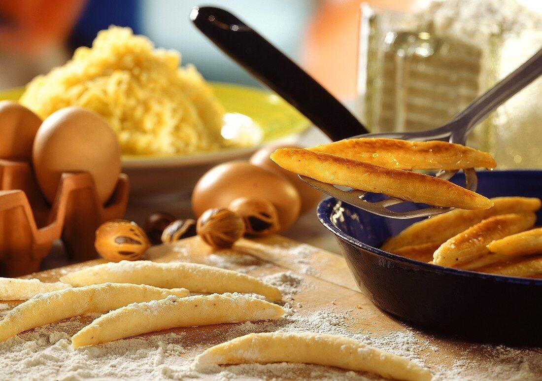Fried potato noodles in pan beside prepared noodles