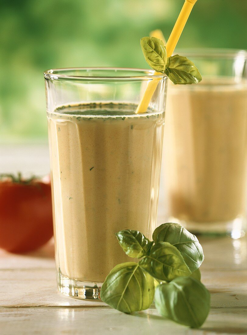 Vegetable drink with herbs in glass with drinking straw & basil
