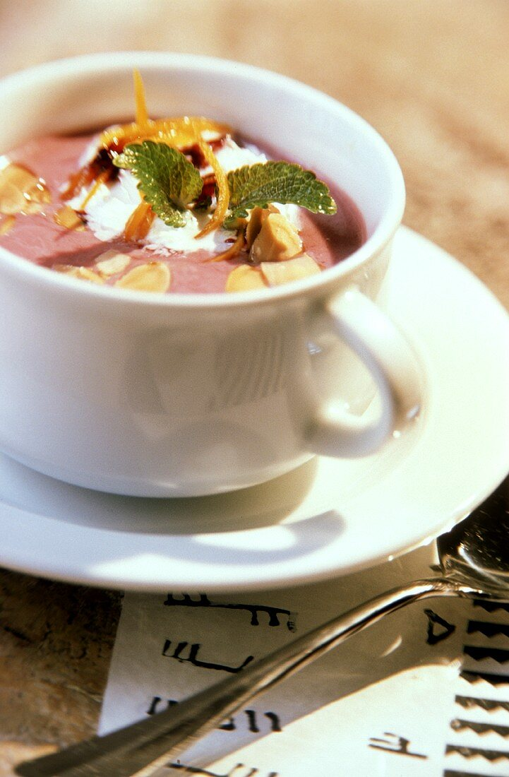Blueberry soup with flaked almonds, cream & mint in cup