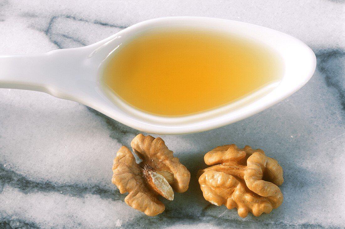 Walnut oil on spoon beside walnut kernels on marble