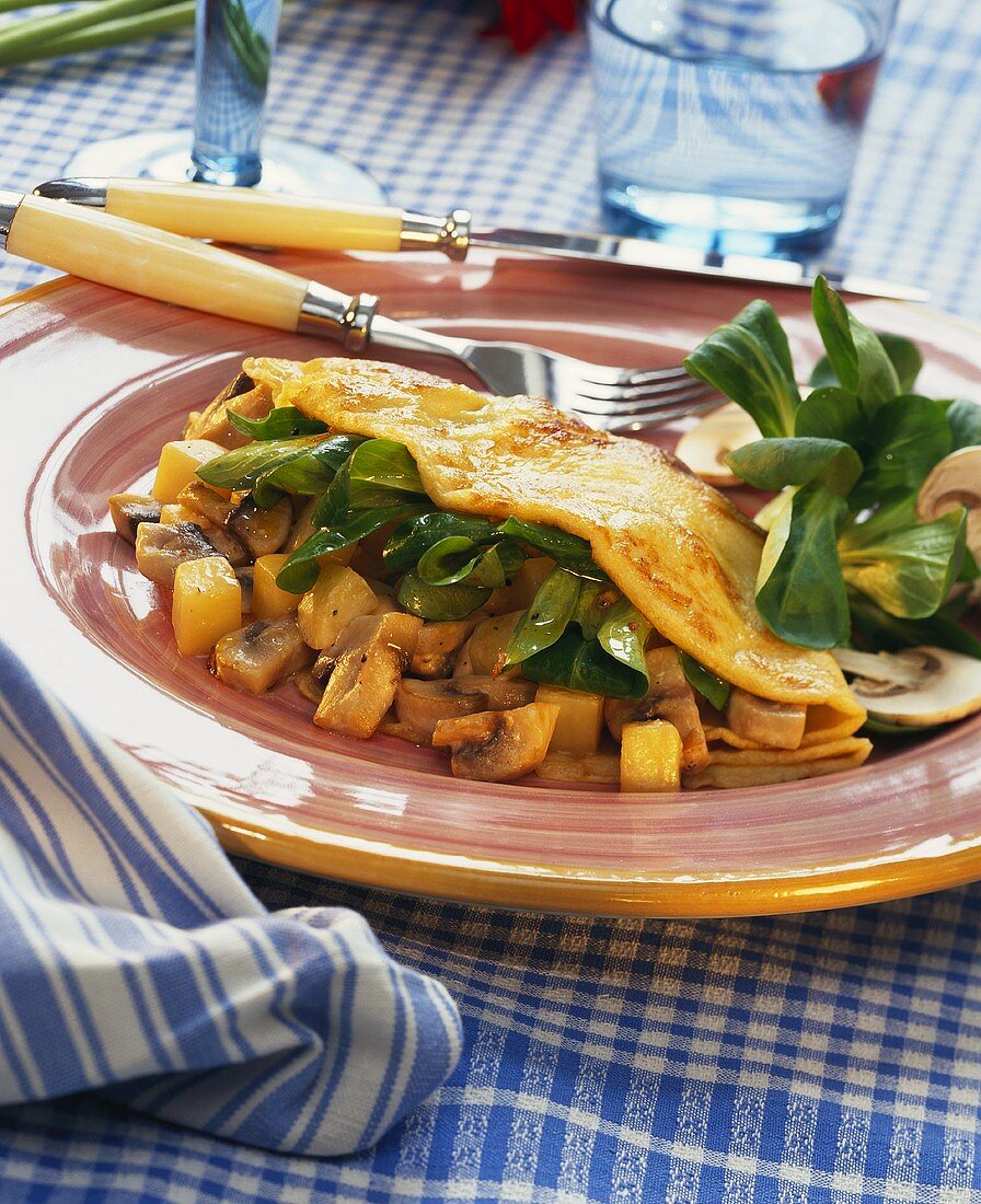 Potato and mushroom pancakes with corn salad on red plate