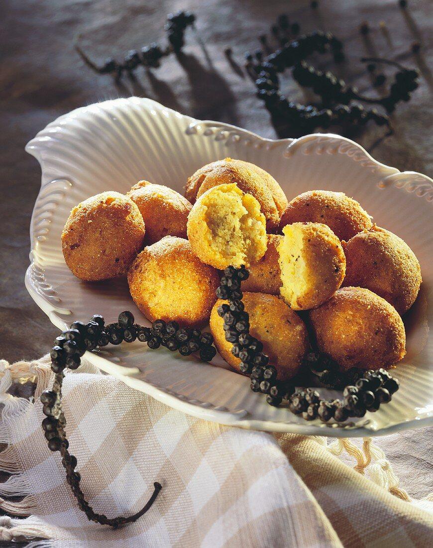 Spicy Hush puppies (sweetcorn balls) on plate; peppercorns