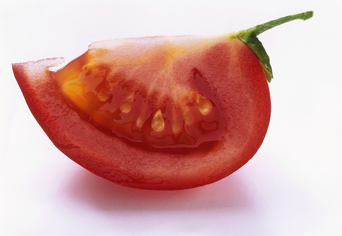 A wedge of tomato with stalk on white background