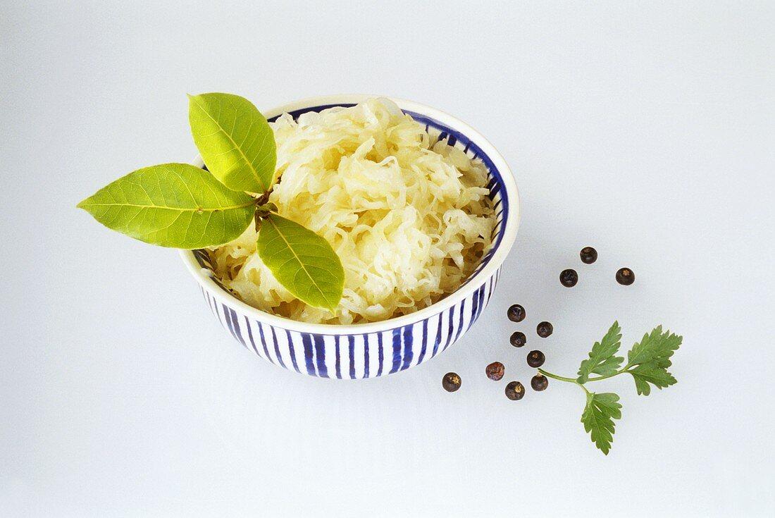 Sauerkraut with sprig of bay in dish; juniper berries