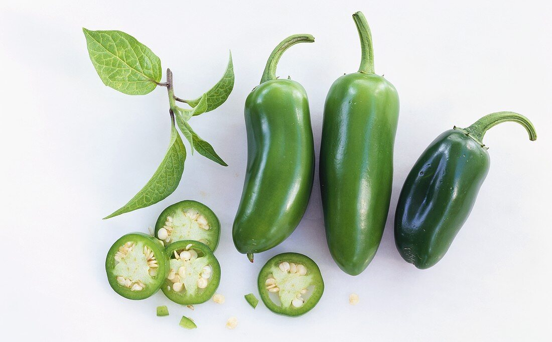 Green chili pepper with slices of pepper and leaf
