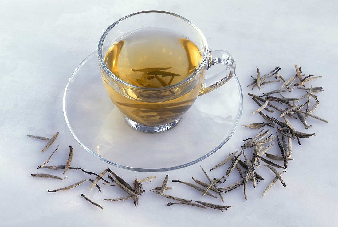 A cup of green tea (Ying Zeng, China) and tea leaves