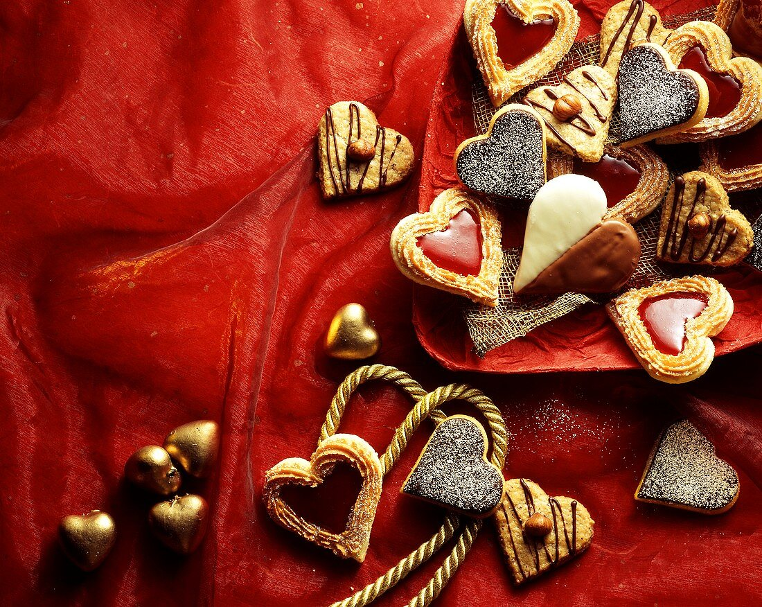 Heart-shaped Christmas biscuits on red fabric and plate