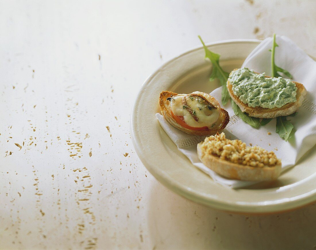 Crostini with rocket mousse, with cheese & tomato & with almond