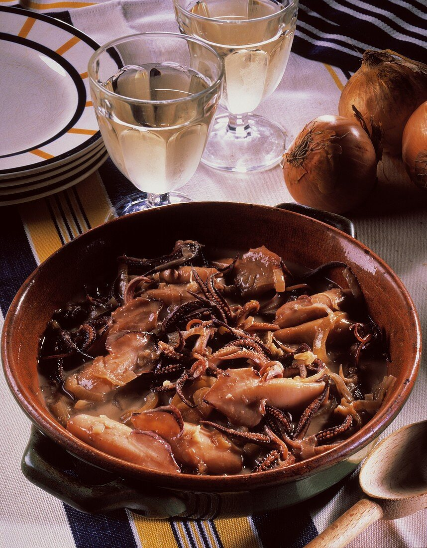 Cuttlefish ragout with onions in ceramic pot; white wine