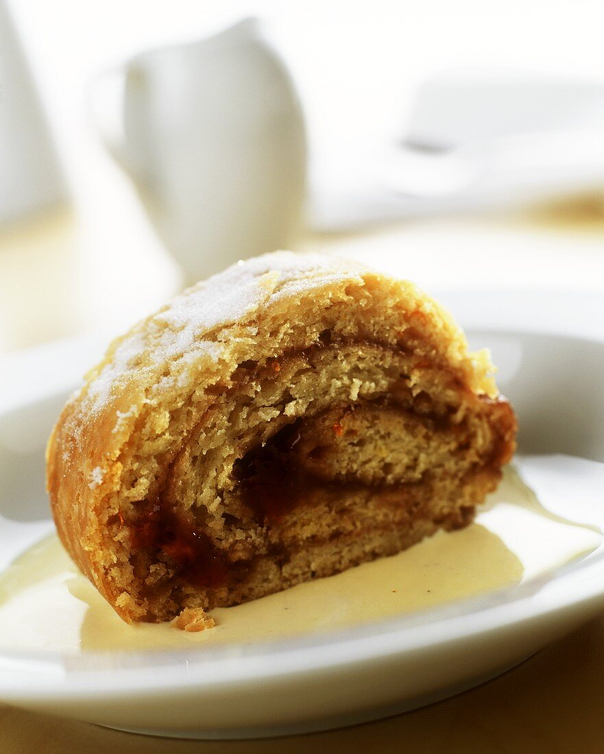 A piece of sponge roll with jam filling on plate