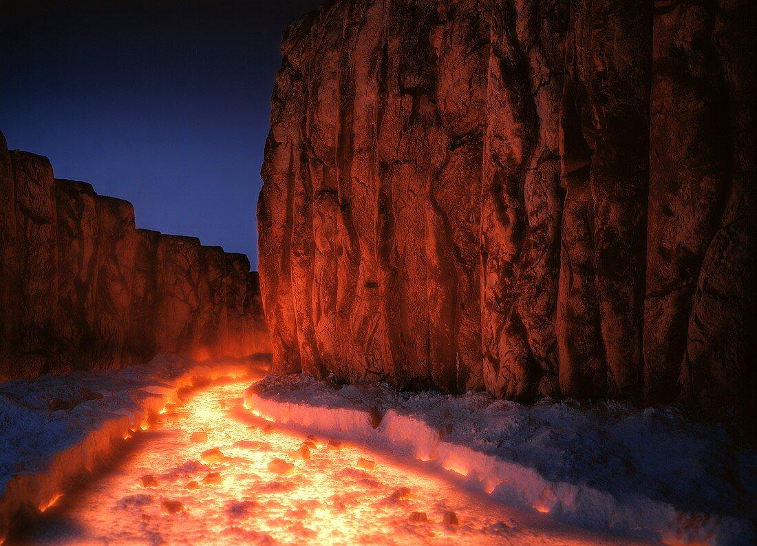 Glowing lava flow between steep rocks