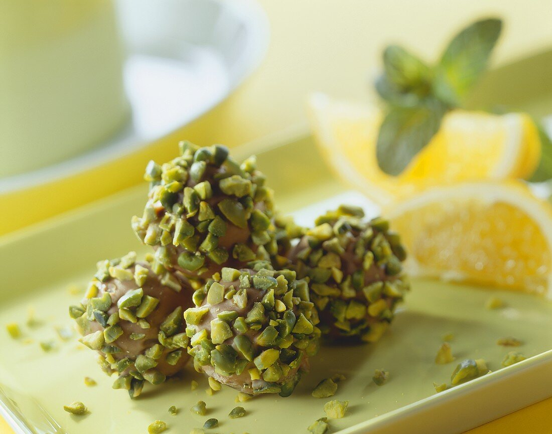 Pistachio and orange pralines on a light green tray