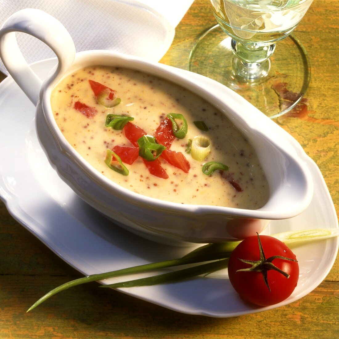 Mustard sauce with tomatoes and spring onions in sauce-boat