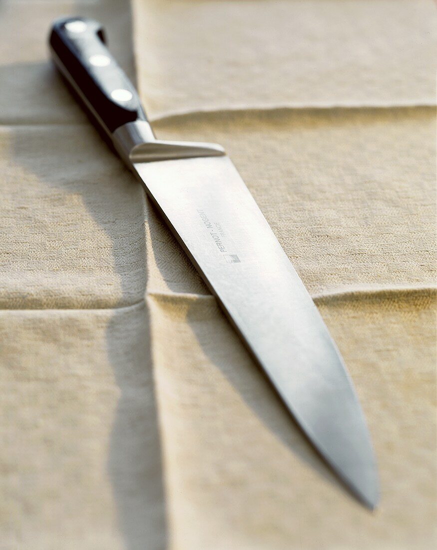 Kitchen knife on a light-coloured table cloth