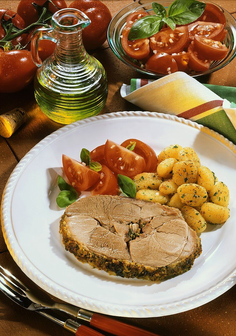 Leg of lamb Roman style with tomato salad and potatoes