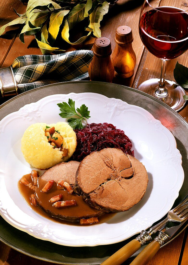 Roast wild boar with dumpling, red cabbage and red wine glass