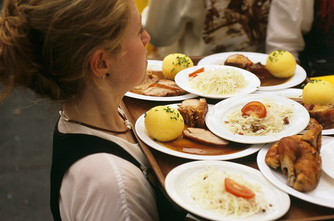 Waitress carrying tray of dishes at Oktoberfest