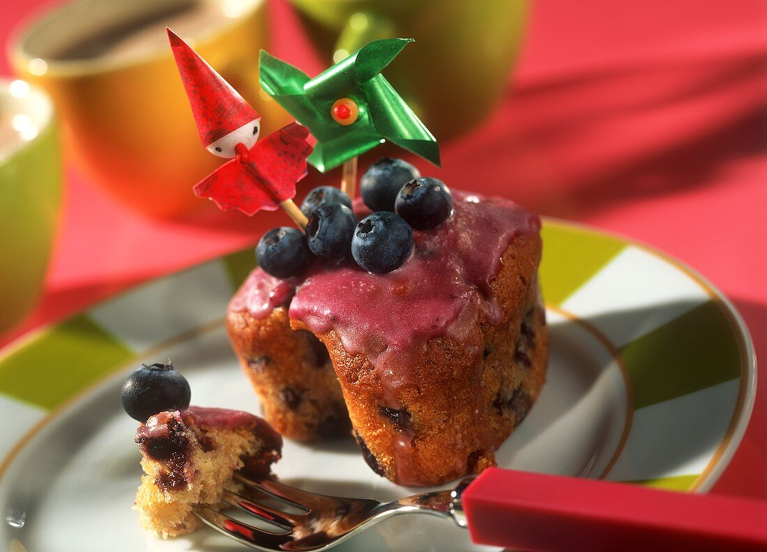 Blueberry muffin with party decorations on a plate