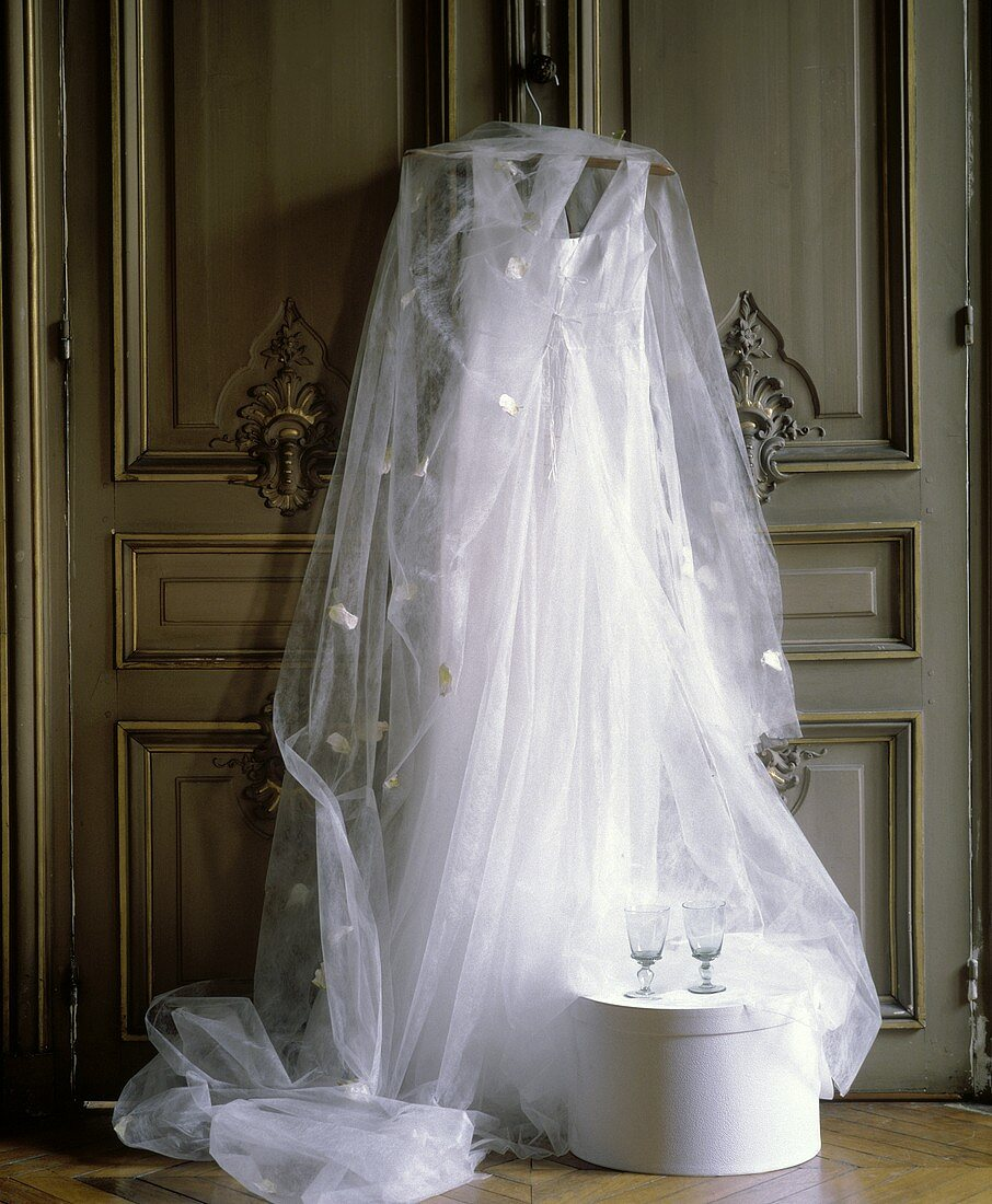 Still life with wedding dress, veil and empty glasses