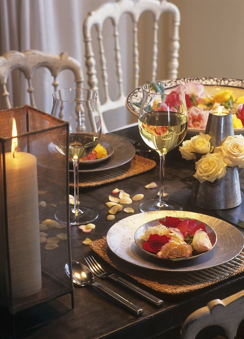 Roses as table decoration, candle and white wine glasses