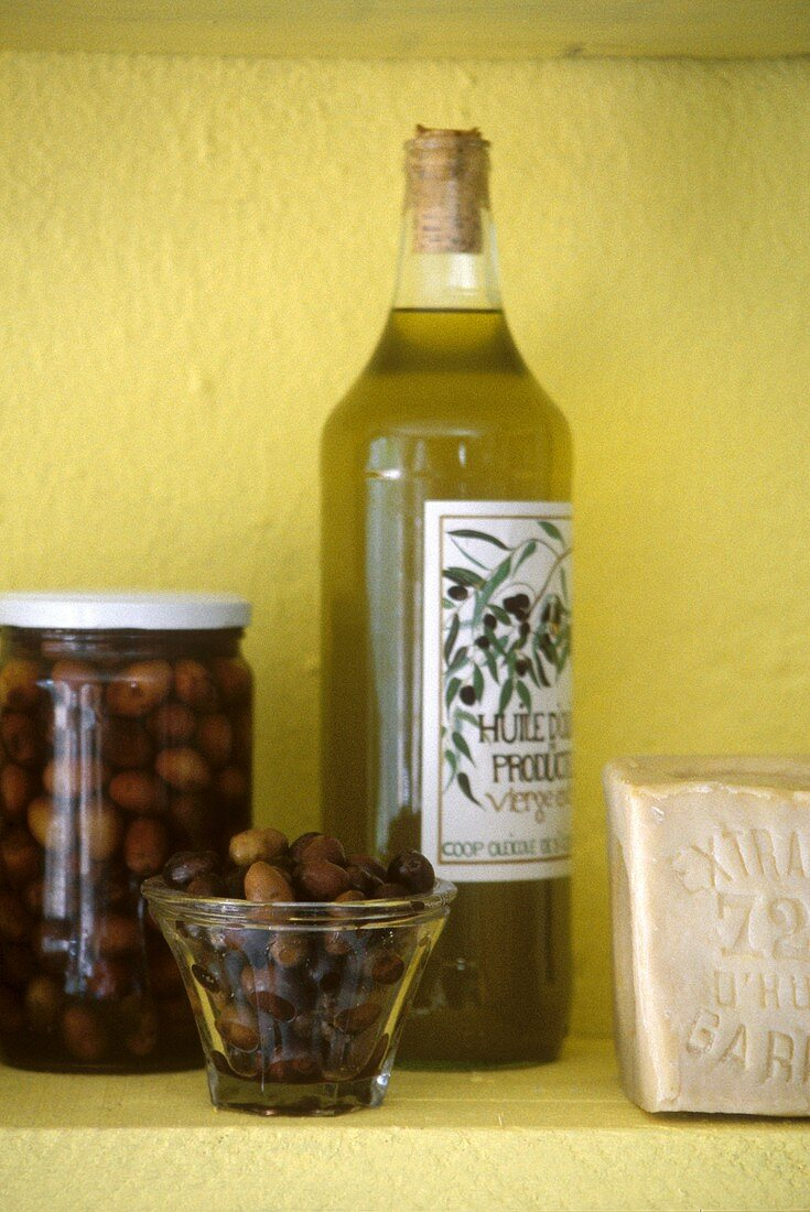Olive oil and black olives against a yellow wall