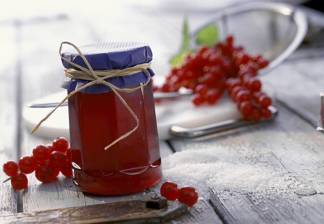 Redcurrant jelly in a jar; sugar, redcurrants
