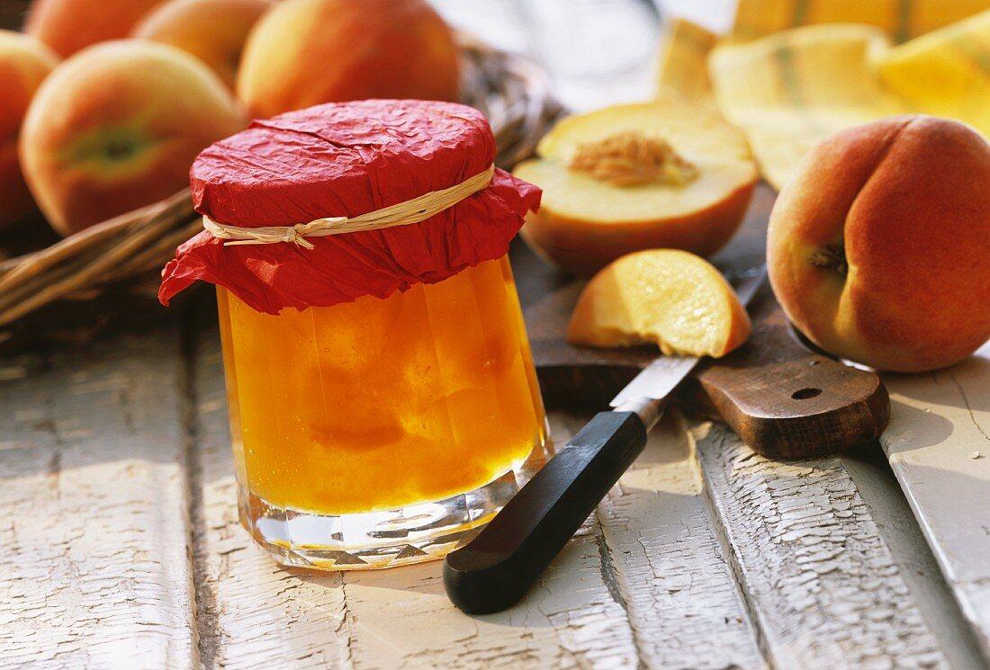 Peach preserve in jam jar in front of fresh peaches