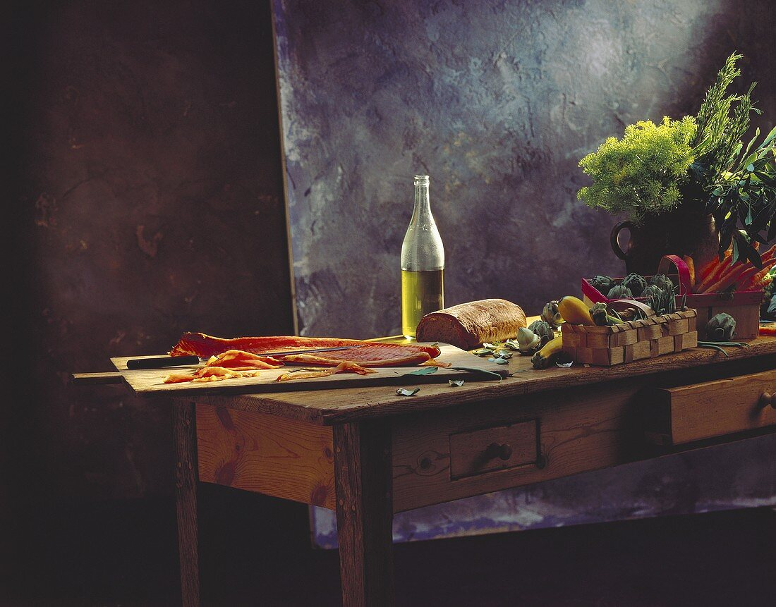 Still life: salmon, olive oil, bread & vegetables on table