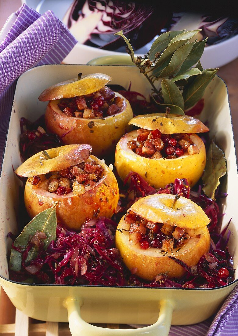 Red cabbage, ham-stuffed apples & bay leaf in a roasting dish