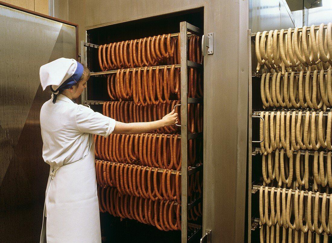 Sausage making: taking sausages out of smoking chamber