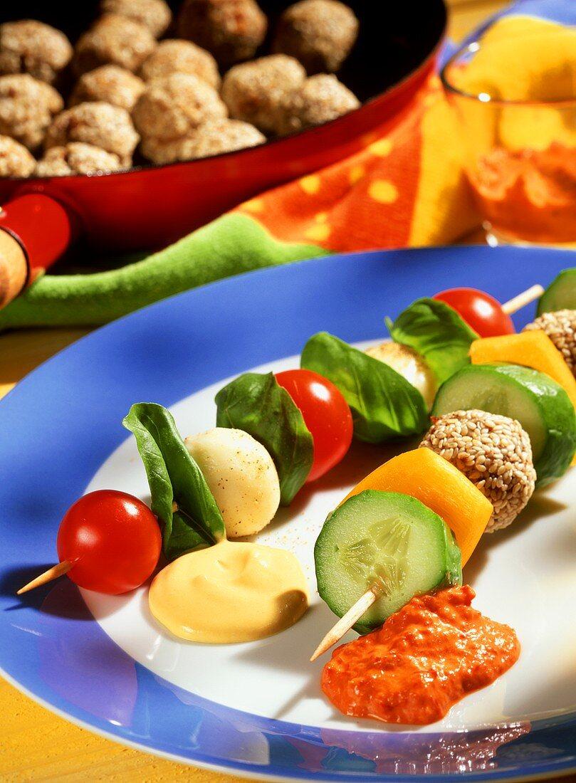 Nibbles on sticks: sesame meatballs, vegetables, cheese & dips