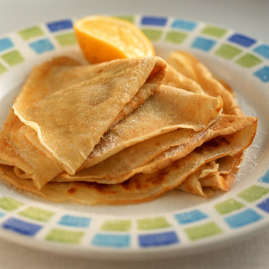 Several orange crepes on a plate