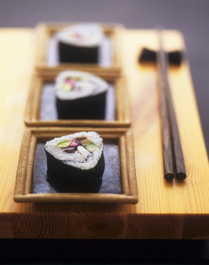 Futo maki in small bowls on wooden board