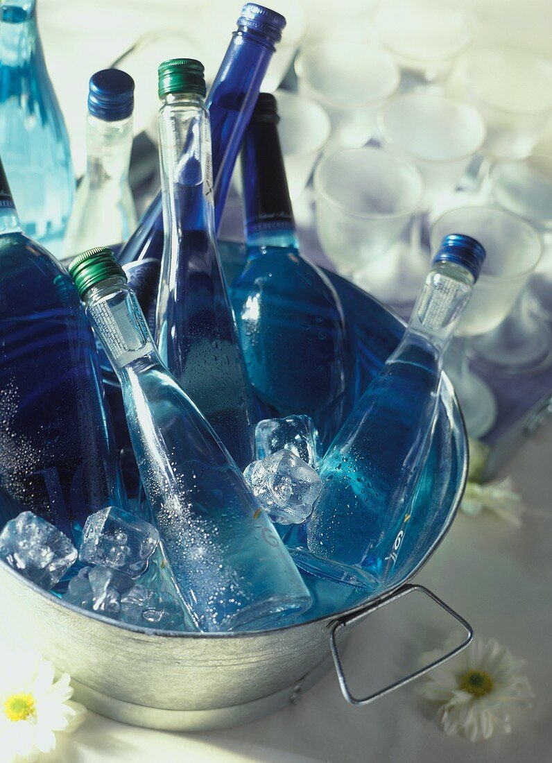 Mineral water- & wine bottles in ice bucket, glasses behind