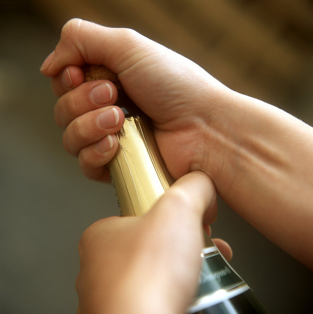 Opening sparkling wine bottle: holding cork firmly in hand
