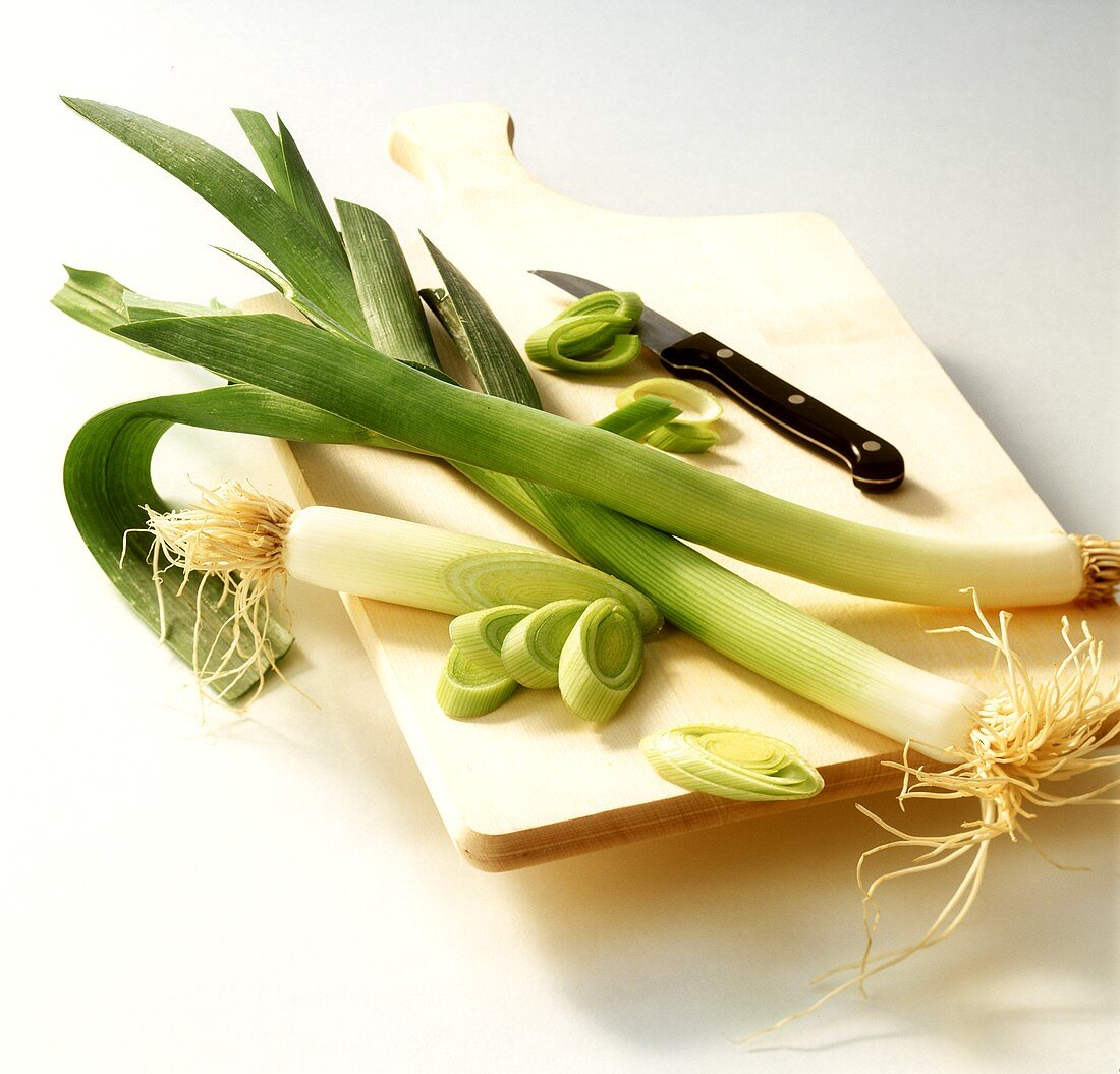 Leek, partially sliced, on wooden chopping board