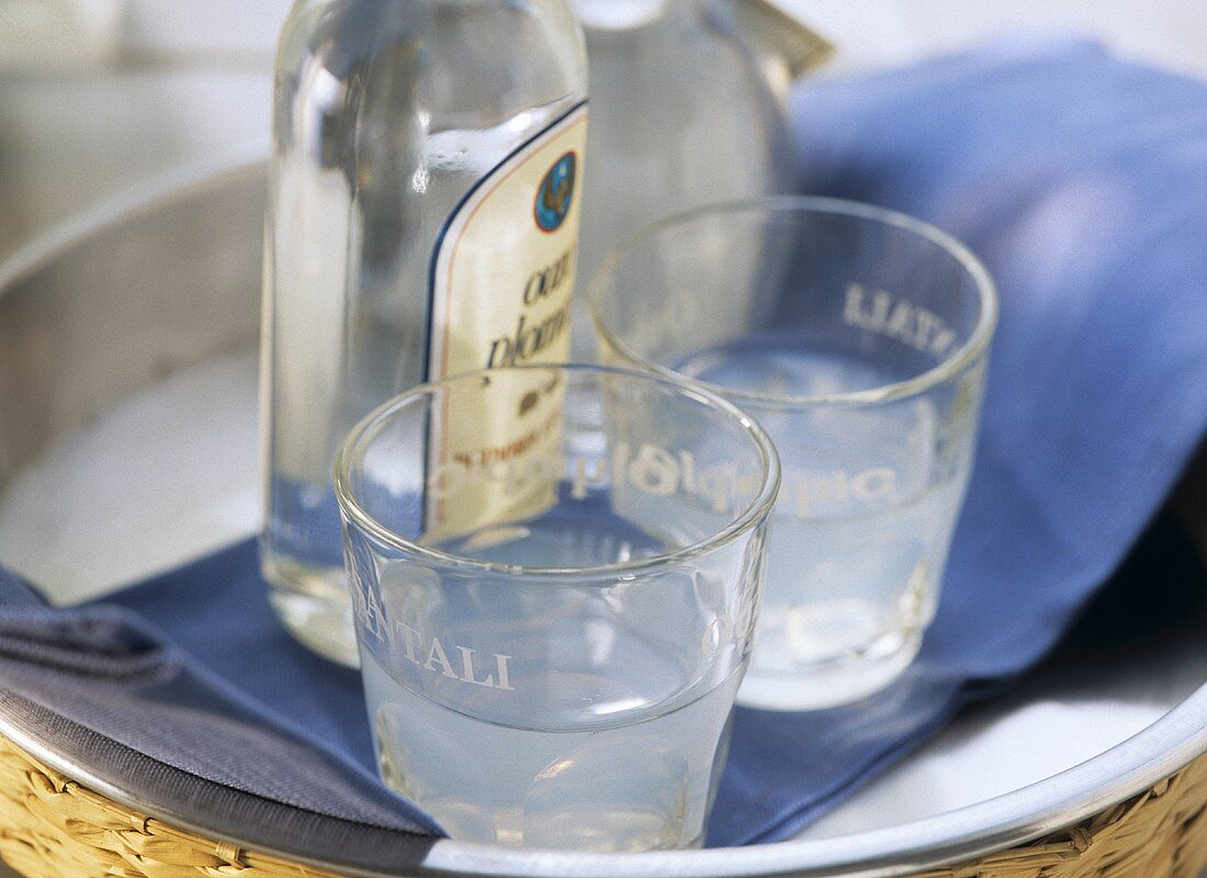 Ouzo in glasses and bottle on tray
