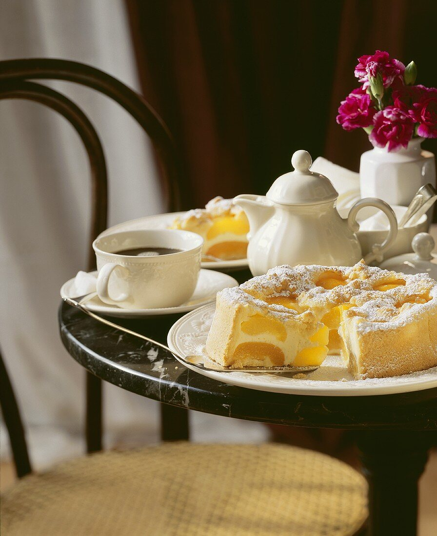 Apricot cheesecake with icing sugar and coffee