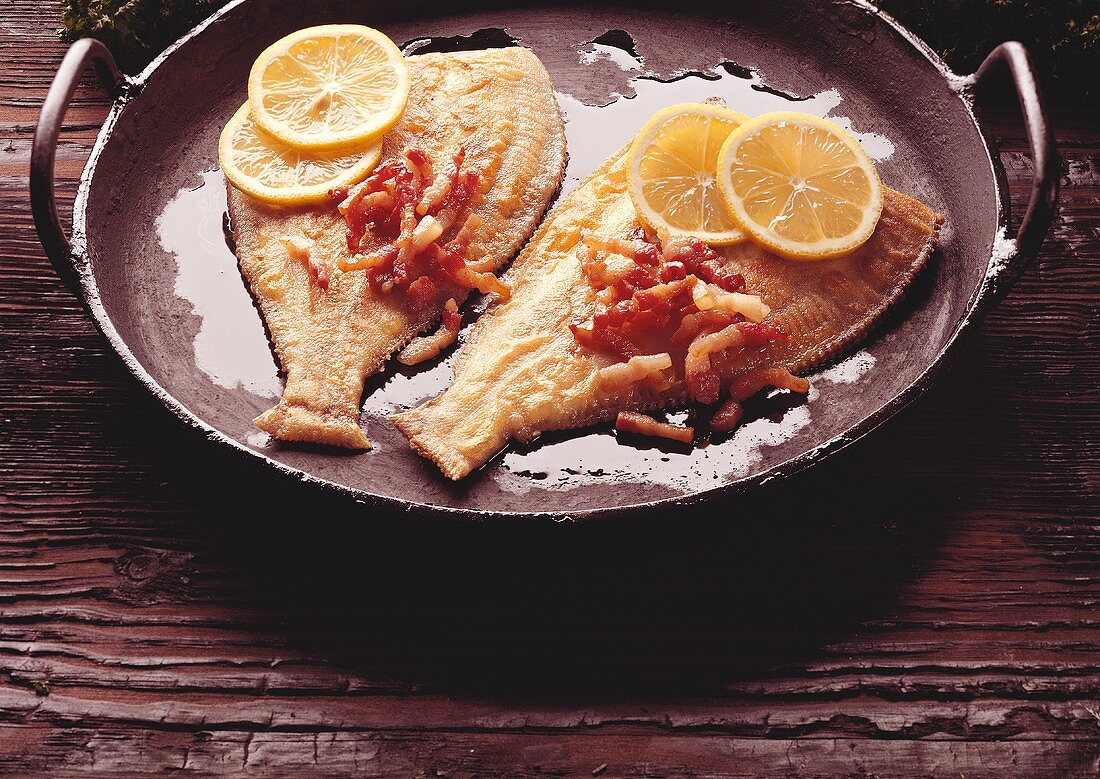 Plaice with bacon with lemon slices on plate