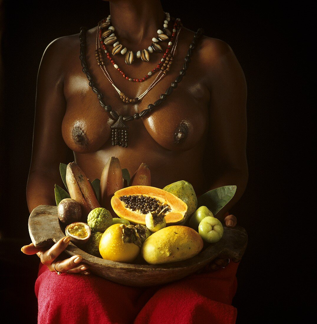 African woman holding exotic fruits in a bowl